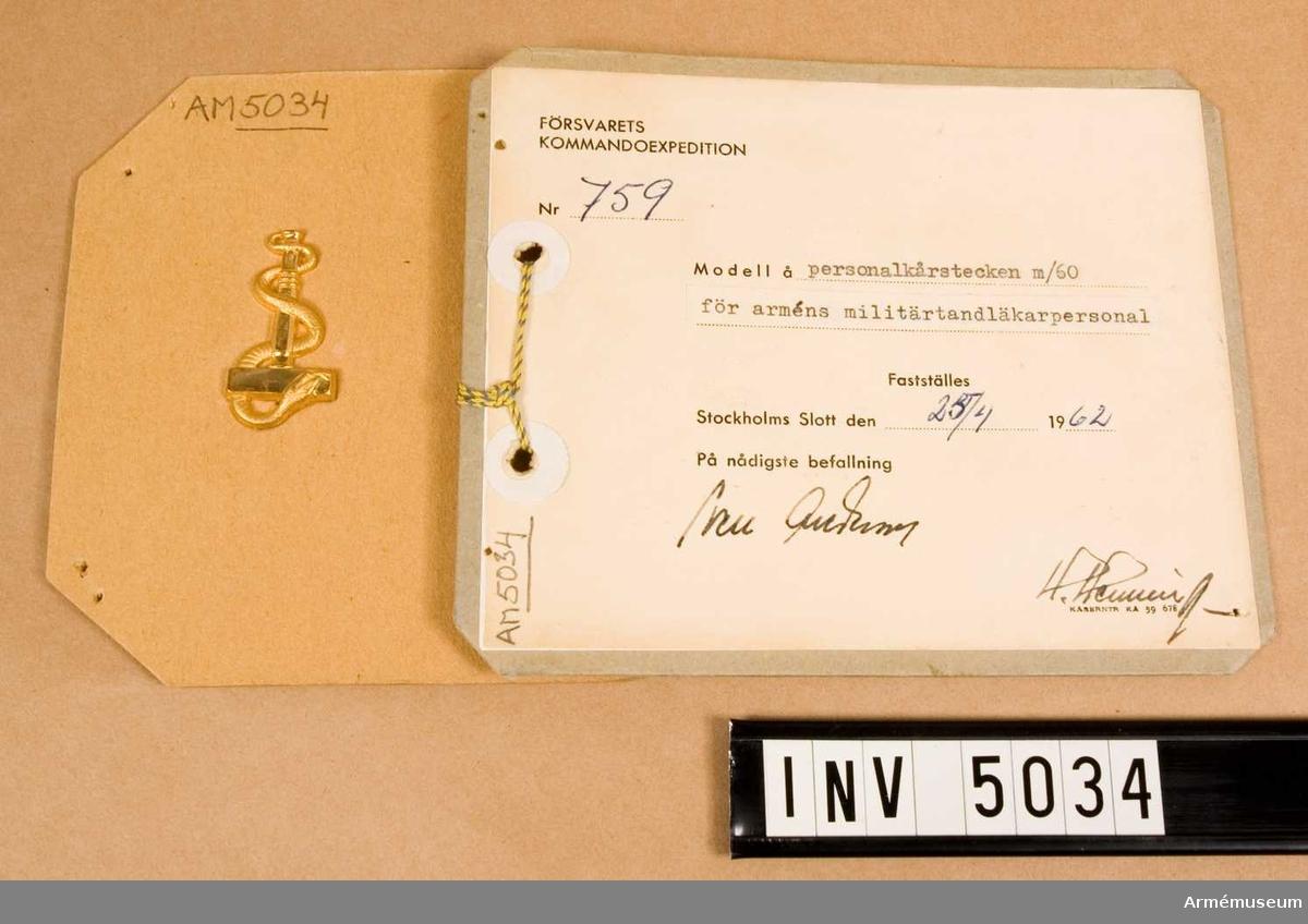 Av metall och i metallfärg m/1960 guld.  Spegelvänt utförande. Den fastställda modellen har här  bibehållits, en T-formad hävel, tandnyckel kring vilken en orm slingrar sig. Tillverkas i två storlekar.