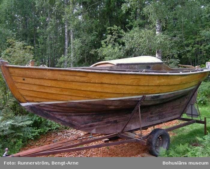 J18 kravellbyggd med ruff. Lackad, vit vattenlinje, rosa/svart bottenfärg. Båten saknar mast och segel. Fäste för utombordsmotor.