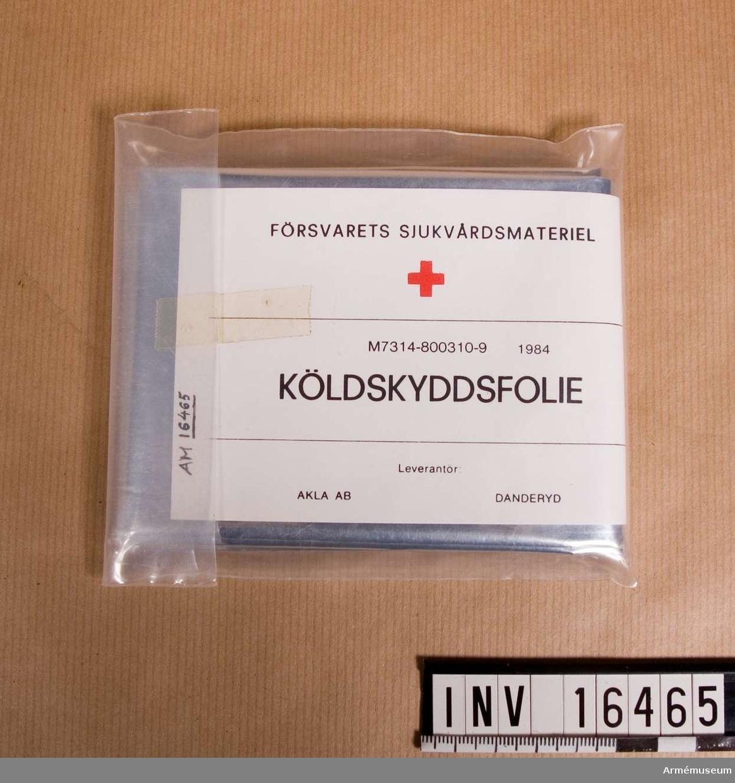 """Köldskyddsfolie M 7314-800310-9.En folie av aluminiserad, något transparent plastmaterial. Storleken är väl tilltagen för att svepa in en skadad person. Folien ligger hopvikt i ett plastfodral med tejp-remsa. I förpackningen finns ett papper med texten """"FÖRSVARETS SJUKVÅRDSMATERIEL"""", rött kors, """"M 7314-800310-9  1984"""" """"KÖLDSKYDDSFOLIE"""", """"Leverantör:"""", """"AKLA AB DANDERYD"""". OBS! Det är svårt att vika ihop folien om den tas ur paketet.Inköpt av Bo Michaelsson vid överskottsförsäljningen 1988-01-16 för 10 kronor."""