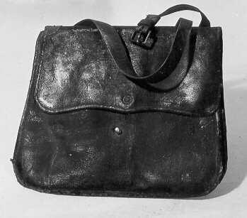 Postväska för gående postbud i svärtat läder. Väskan försedd med ställbar bärrem. Över öppningen viks en klaff som fästas på framsidan runt en metallknopp.
