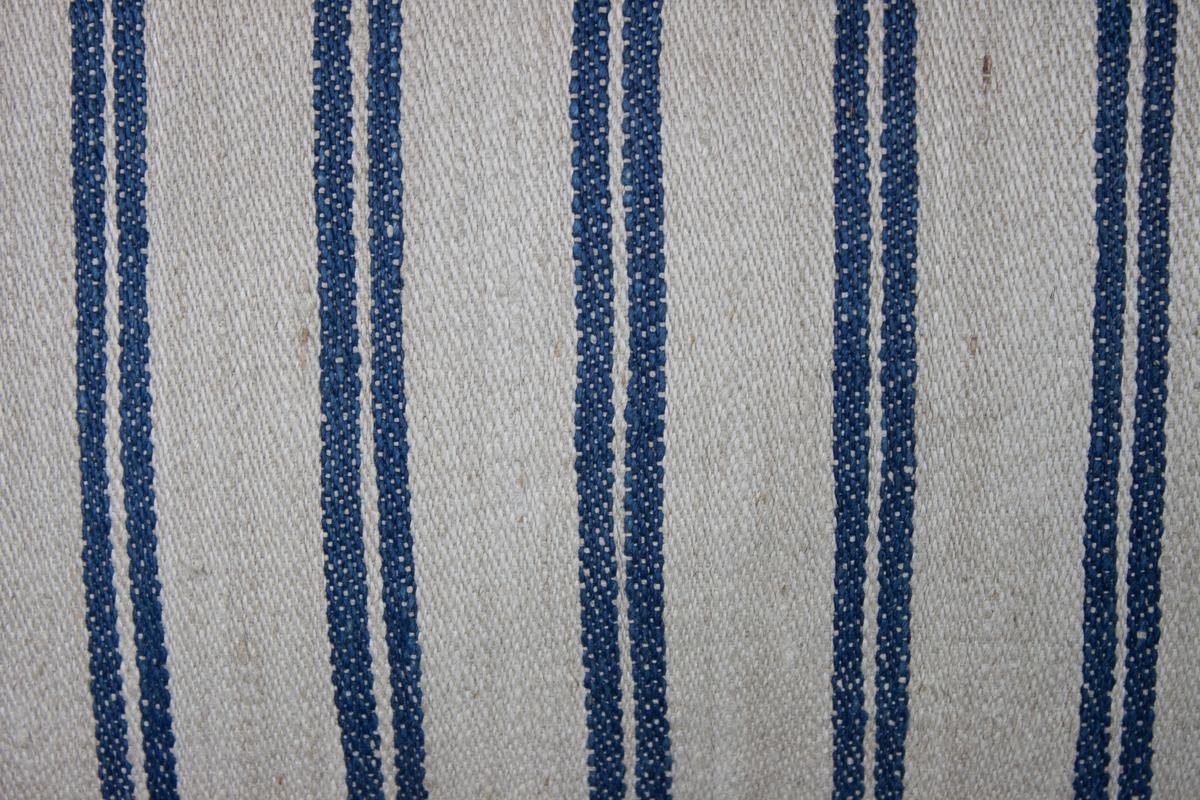 Kudde, tillverkad av handvävt linnetyg, kypert på tre skaft, med vit varp och inslag i något tjockare lingarn i vitt och blått.  Fyllning: fjäder.