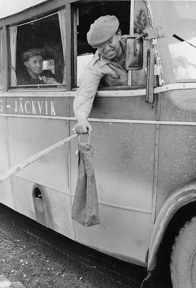 Chauffören tar en postsäck som uthängts vid vägen.