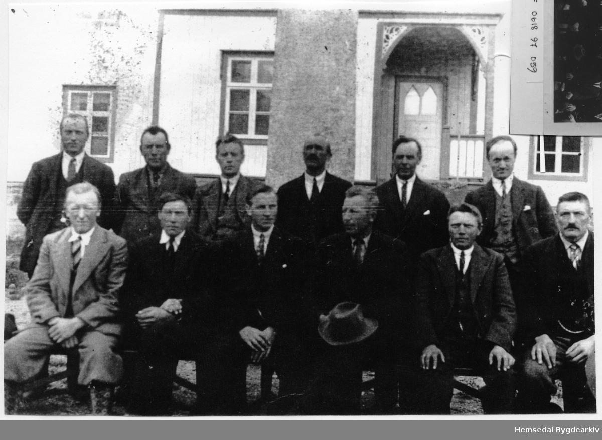"""Kommunestyret - Heradsstyret 1935 - 1937. Fyrste rekke frå venstre: Ola Flaten, Peder L. Markegard, Nils Hulbak, Ola E. Ålrust, Ola A. Finset og Ingvar Gjærde. Andre rekke frå venstre: Ola L. Lien, Embrik Skar, Østen Torset, Nils H. Eikre, Ola P. Embre og Trond Haug. Eit sitat etter Embrik Skar i denne samanheng : """" Dæ ha vørte so moderne å skjældre se (fotografera seg), no måta.""""  Biletet er teke framfor den gamle Tingbygnaden (Heradshuset) som låg om laag der Kyrkjestugu og biblioteket ligg i dag (2013). Bak kommunestyrerepresentantane står minnesmerke som kring 1980 vart flytta inn på kyrkjegarden."""