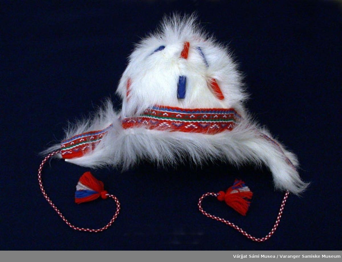 Barnelue av hvit geiteskinn. Pyntet med små kledebiter i rødt og blått. Pynteband , vevd band rundt kanten av lua. Snorer av ullgarn.