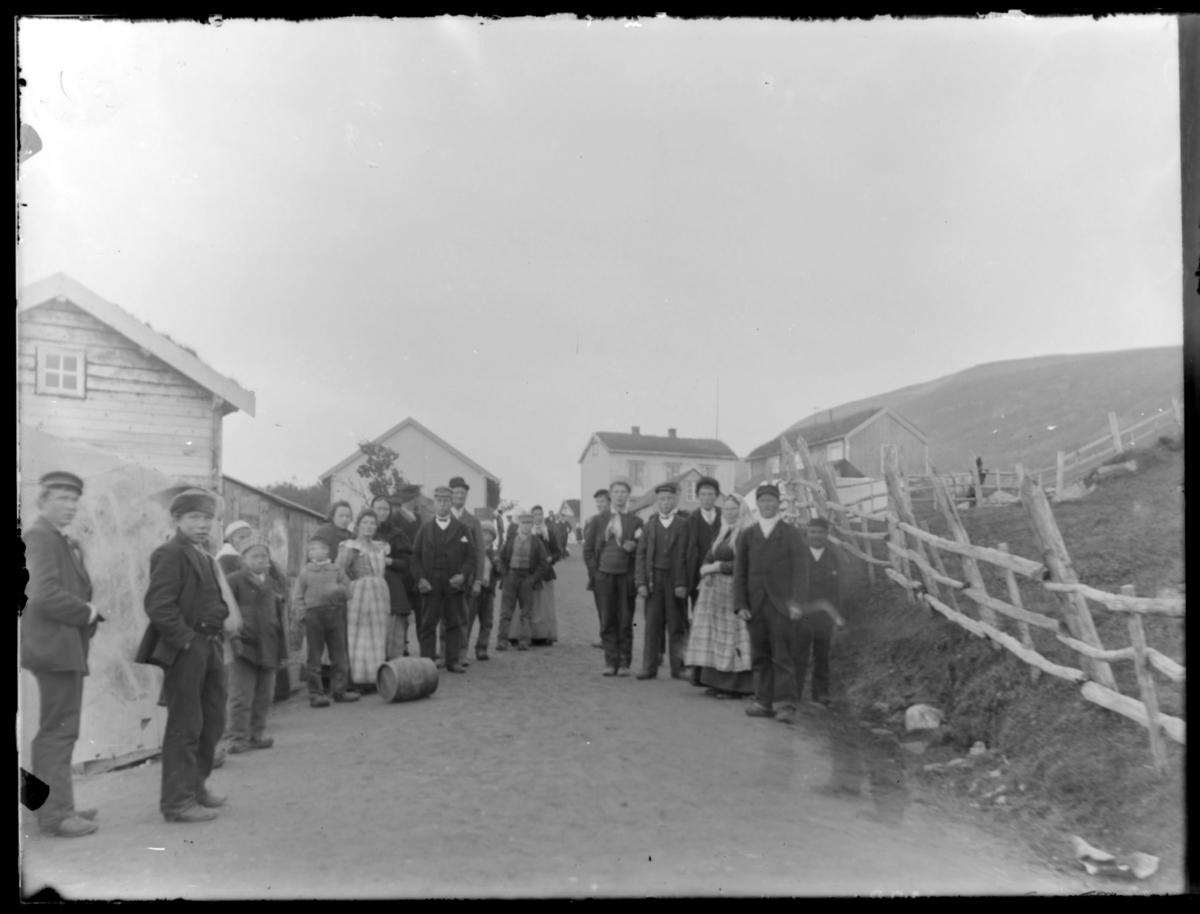 Mennesker langs grusveien ved markedsplassen på Langnes. Dette bildet er tatt i Langnesbakken, veien ned til elva. Huset til høyre er folkeskolen. Huset midt på bildet - her var det telegraf og kommunestyresal.