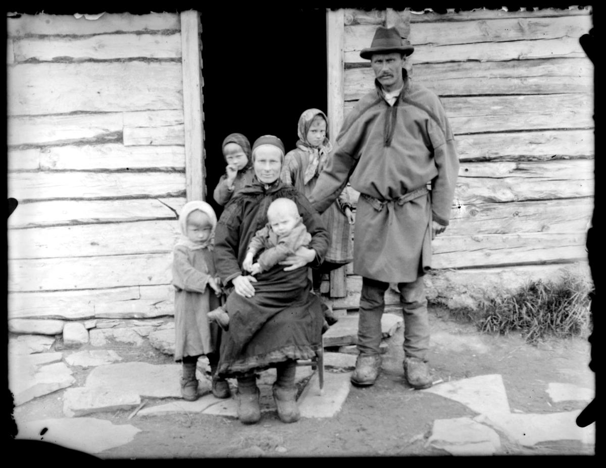 Samisk familie fotografert på trappa utenfor huset sitt
