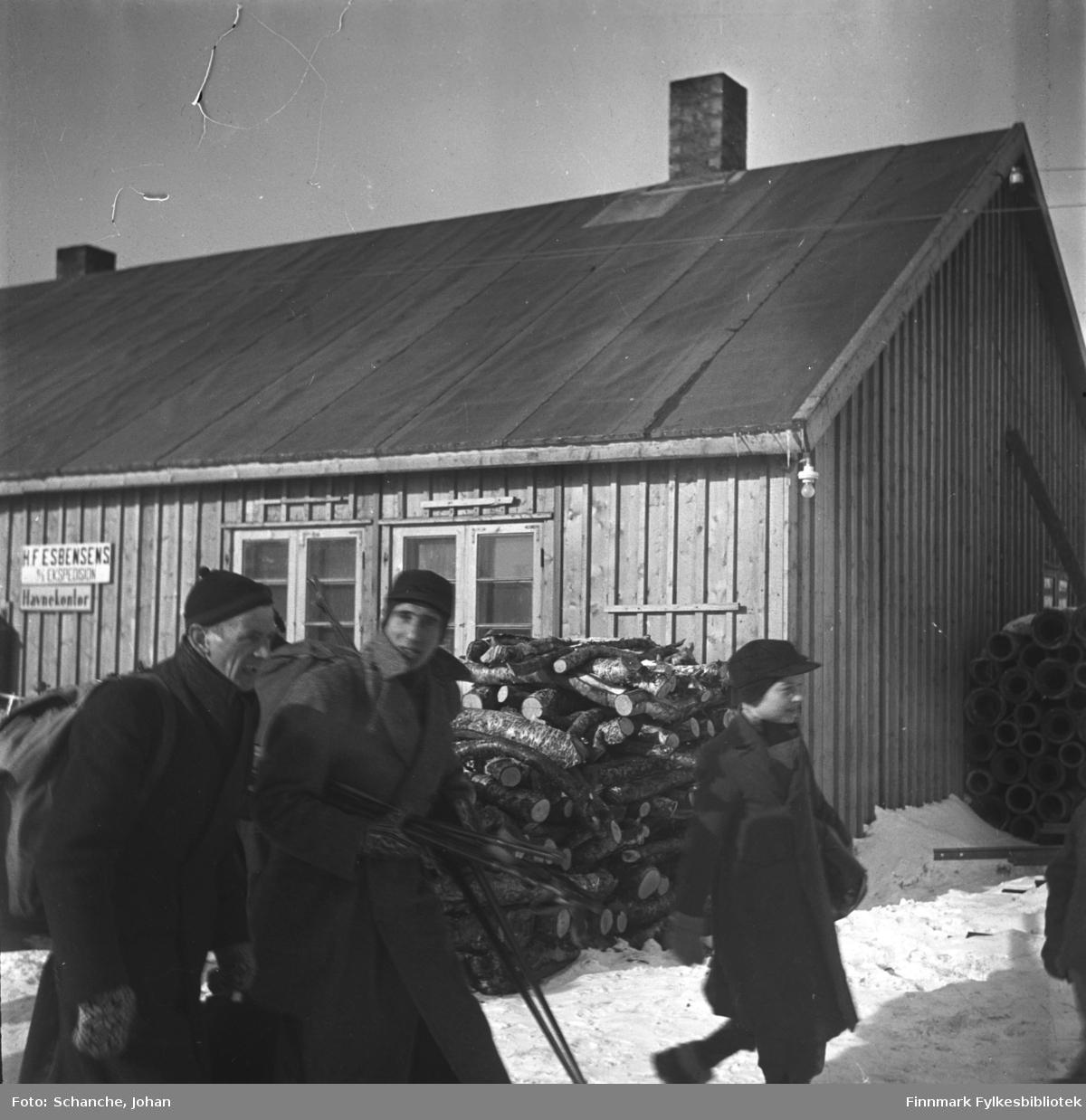 Olav Økern og truppsleder Nordli ankommer til Vadsø for å delta i kretsrennet. Mars 1946. Olav Økern har ryggsekk på seg. Begge er kledt i lange frakker. En gutt går foran dem i lue og frakk. Bak ser vi en bygning. Det er to skilt på veggen. 'HF Esbensen' står det på det ene, 'H....kontor' på det andre.