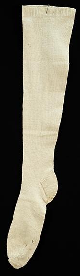 Hvit strikket Knestrømpe. (1 stk). Strikket på tynne pinner. 2 cm vrangbord 2r, 2vr. deretter glattstrikk. Fasongstrikket legg, felling langs vrang maskerad midt bak begynner 12 cm nedenfor vrangbord og slutter ved helfelling . Monogram i korssting under vrangborden. Slitasjehull ved stortåa. To små hull og små rustflekker under foten. Ellers god stand