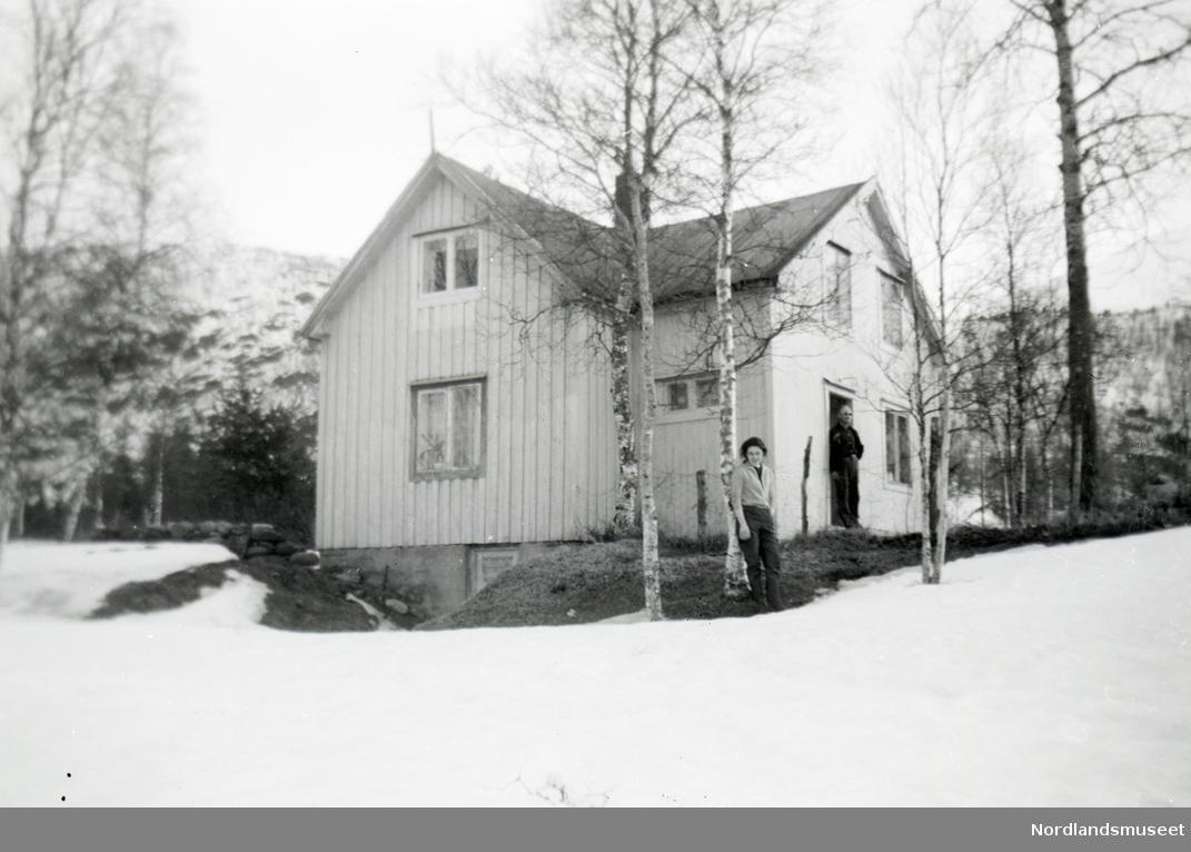 Lysemalt hus. Stående panel.  Mann i dørkarmen, ung kvinne under trær foran huset.  Vår?