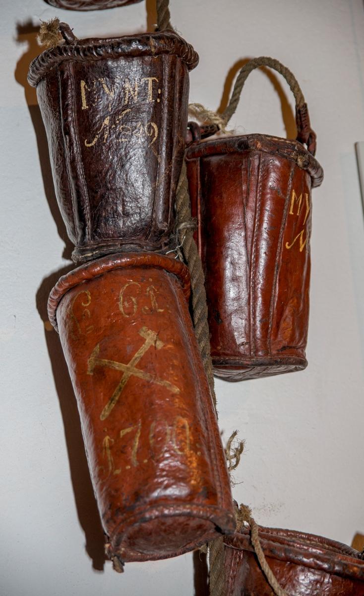 Brannbøttene er laget av to eller flere lærdeler som er sammenføyet med søm. Det er sydd inn to tre-spiler, som går fra kanten av bøtteåpningen og og ned til bunnen. Disse er plassert vis-a-vis hverandre i forhold til bøttens diameter. Trespilene fungerer antagelig som forsterkning både av bøtten og hankefestet. Bøttene er malt med rødbrun farge både utenpå, inni, og i bunnen. Overflateundersøkelse med mikroskop viser et tynt malingslag. Malingen har trengt inn i porene i læret. Bøttene er påført nummer, eierbetegnelse og årstall med gulhvit maling. Alle malingslag fester godt til underlaget. Læret er stivt og hardt. Bøttene har vært innsatt med bekk innvendig for at de skulle være vanntette og det finnes enda rester av bekk på noen av dem.