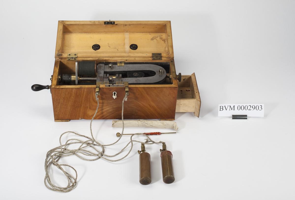 Skrin med innebygget elektrisk apparat. Skuff med 2 metallsylindre (kobber?) Lengde 7 cm, diam. 2,4 cm. Tilkoblet apparatet ved flettet hvit metalltråd. Papirlapp i skuffen med påskrift Dr. Poulsen. Et messinginstrument, se BVM 2904.