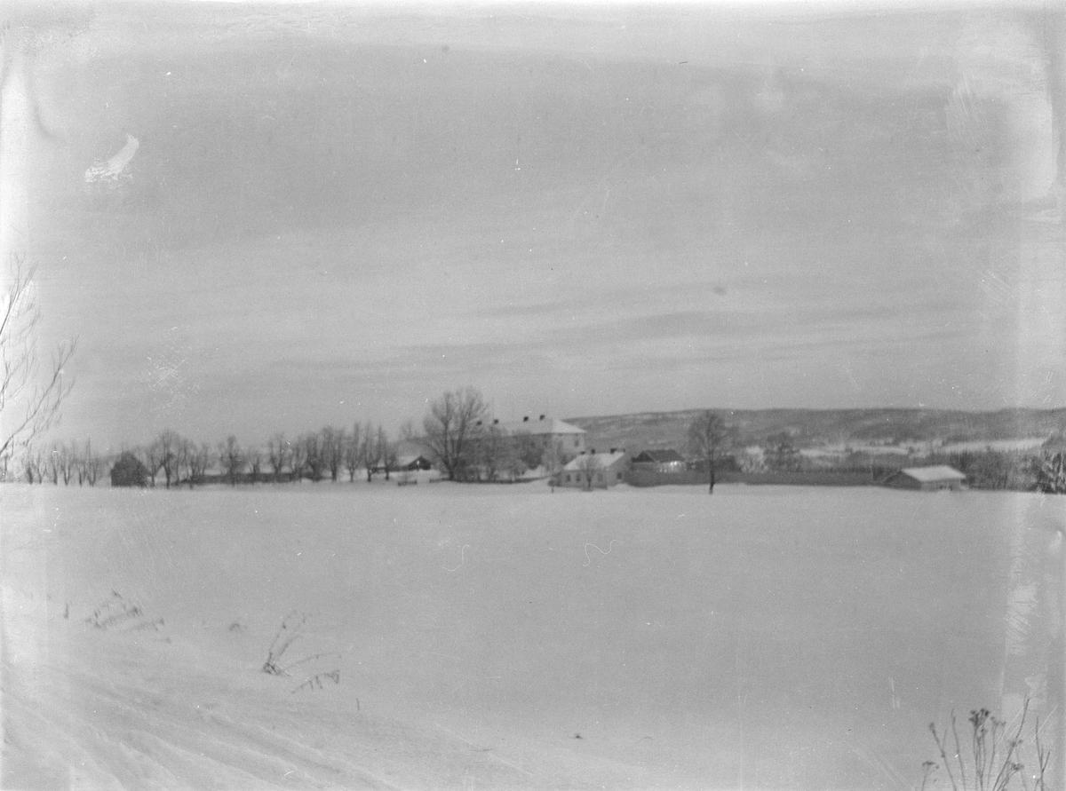 Linderud Gård med hele gårdsanlegget sett fra avstand med snødekte jorder i forgrunnen.