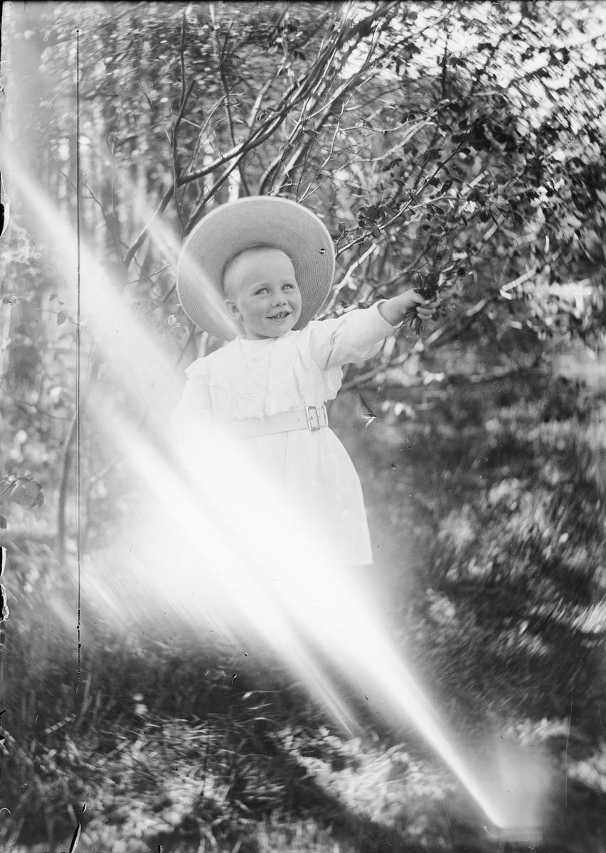 En smilende gutt strekker hånden frem og i den har han blomster. Han står i gresset med en bakgrunn av busker og trær.