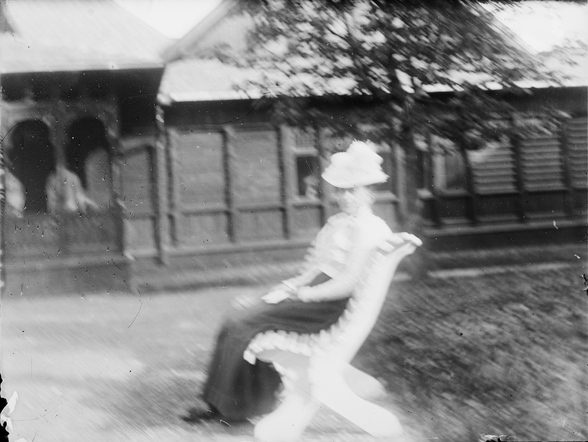 En dame sitter på en hagebenk utenfor et hus bygget i sveitser-/ dragestil. Benken står på en gruslagt plass i en opparbeidet hage. Under husets svalgang sees to andre personer.