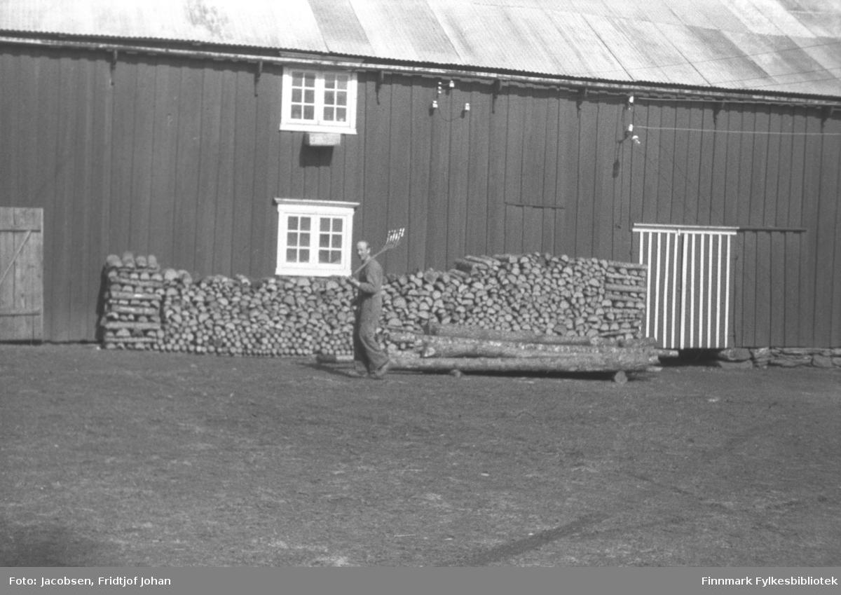 En mann iført ganske lys kjeledress går forbi en stabel med ved som ligger inntil en hus- eller fjøsvegg. Han har arbeidsklær på og bærer en spade eller lignende over skulderen. En stor, åpen plass foran på bildet, har grusdekke og noen tømmerstokker ligger foran vedstabelen. Sprossevinduene på langveggen har hvite, brede kamer og lister. Taket på bygningen ser ute til å ha bølgeblikk-dekke.