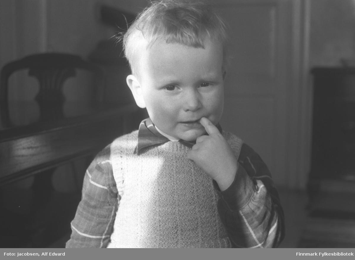 Arne Jacobsen fotografert i Televerkets hus på Storvannsveien. Sola skinner inn på hans høyre side. Han har en rutet skjorte og en strikket vest på seg. Et ganske mørkt bord og en stol ses til høyre på bildet. Noe diffust kan et mørkt skap ses bak hodet til Arne. Til høyre står et skap/sjenk og til venstre for det står en lys speildør med brede karmer.