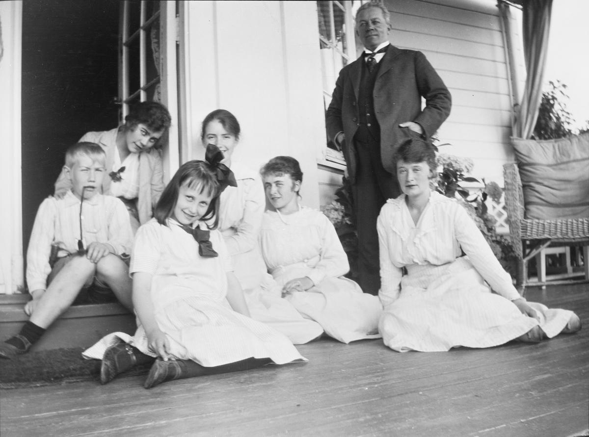 Fem kvinner, fra jente til voksen, sitter på verandagulvet: Eva Gleditsch (foran), Astri Blehr (bak), Hedvig Vetlesen og Else Vetlesen. Bak Iacob sitter Celina begge på et trappetrinn. Bak de andre står Christian Pierre Mathiesen.