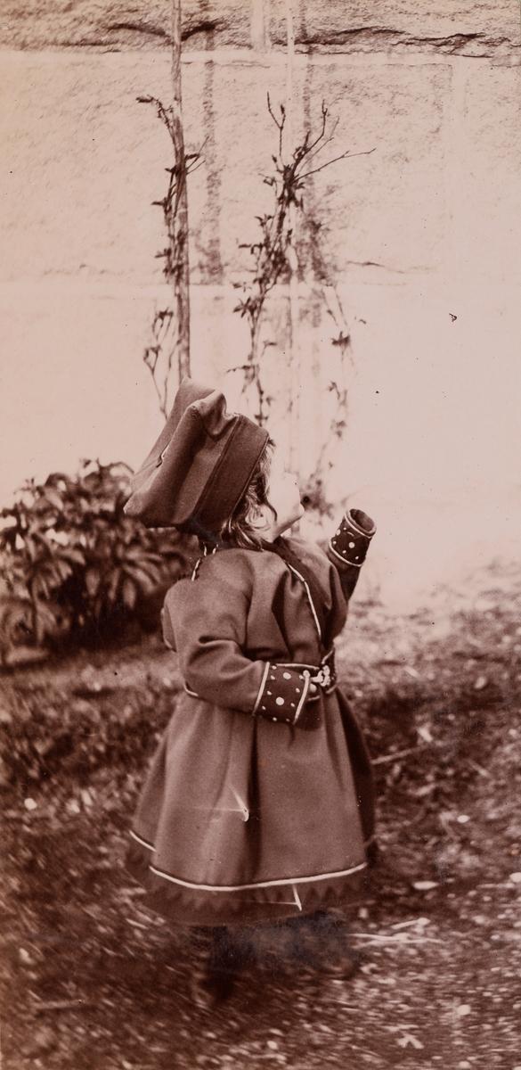 Et lite barn (trolig Eva Mathiesen) i samedrakt.