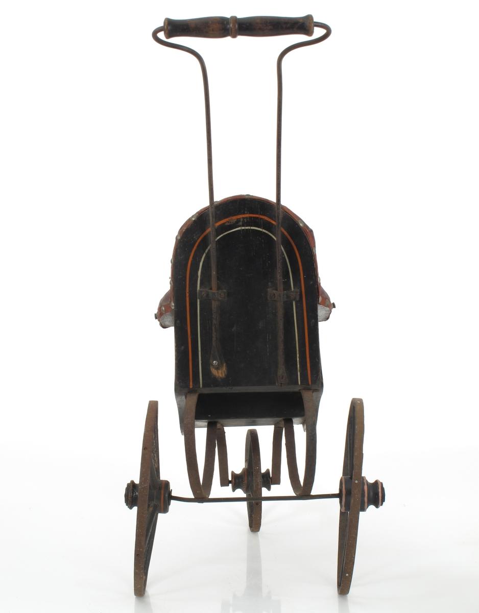 """Sortmalt """"sportsvogn"""" dekorert med engelskrødt og  gult, stoppet sete, lener og rygg, trukket med  burgunderfarget oljelerret som også fotbrettet, kantet med røde  blomullsbånd med messing  stift.  Et lite forhjul, større sidehjul med eiker av tre.  To jernstenger danner håndtak med dreiet sortmalt  holder."""