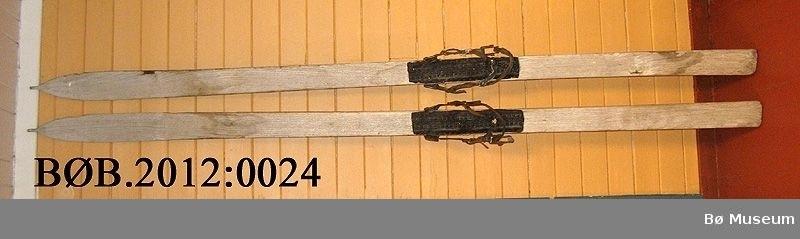 Heimelaga treski. Det er laga hol gjennom skia for å feste bindingar. Det er spikra på uppskorne sykkeldekk bak bindingen. Den eine skia er reparert eller forsterka med ein liten metallbit som er spikra på. Skia har to rendar under.