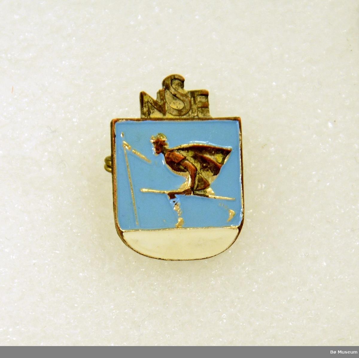 """Pin - med innskrift): """"NSF"""" (Norges Skiforbund) I metall og emalje. Med nål bak."""