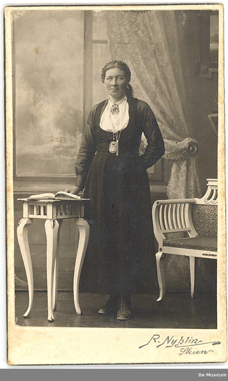 Gunhild G. Strand, Gvarv, i stakk og liv, ståande i fotoatelier.