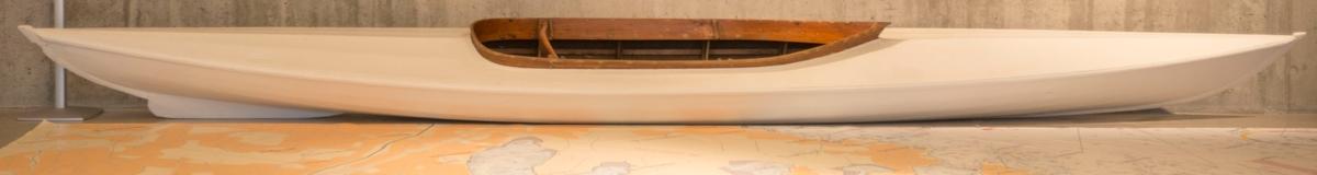 """Hvit tomannskajakk med én lang """"kabin"""". 12 kg. Bygd for padlere opptil 75 kg. Spiler og spant av tre. Seilduk (skrog)."""