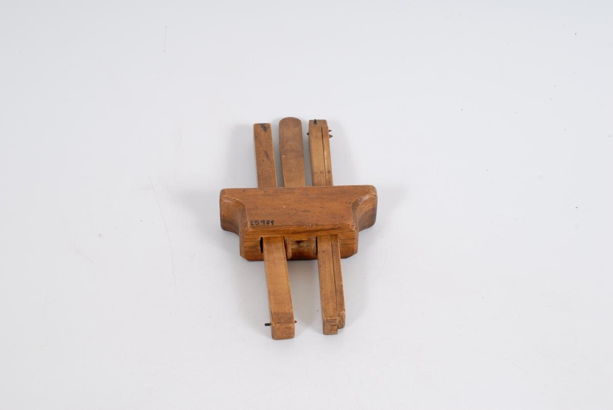 """Mål: Kloss: H 4,8  L 12,5  B 3,7. L pinne 23,5  Gr.fl. 1,7 x 1,6. Kraftig trekloss som smalner nedover. Har 2 huller for rekt. pinner som festes m/to små kilepinner, som grades fast. Stor kile mellom pinnene """"låser""""for det ønskede mål. Den ene pinnen kan forlenges (not og fjær system). Små stifter ytterst på pin- nene for rissing."""