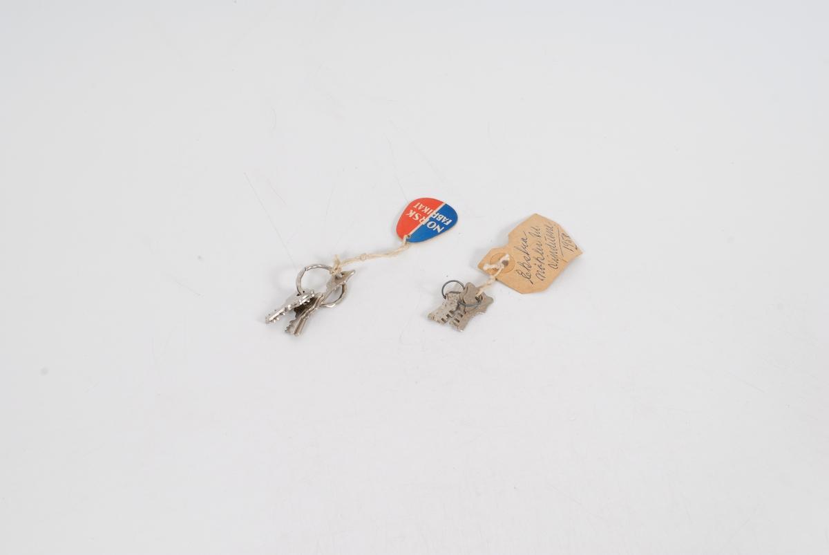 Form: 9 nøkler fordelt på to knipper; En ring med fem nøkler på, og det andre er fire nøkler parvis på hver sin ring forbundet med hyssing. Begge har en merkelapp bundet til seg.