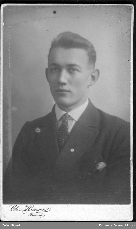 Portrett av en ung man antagelig fra Langfjordhamn i Loppa kommune. Han er kledd i dress: jakke, skjorte og slips. Han har trolig et tørkle i lommen. Bildet trolig tatt rundt 1900-1920.