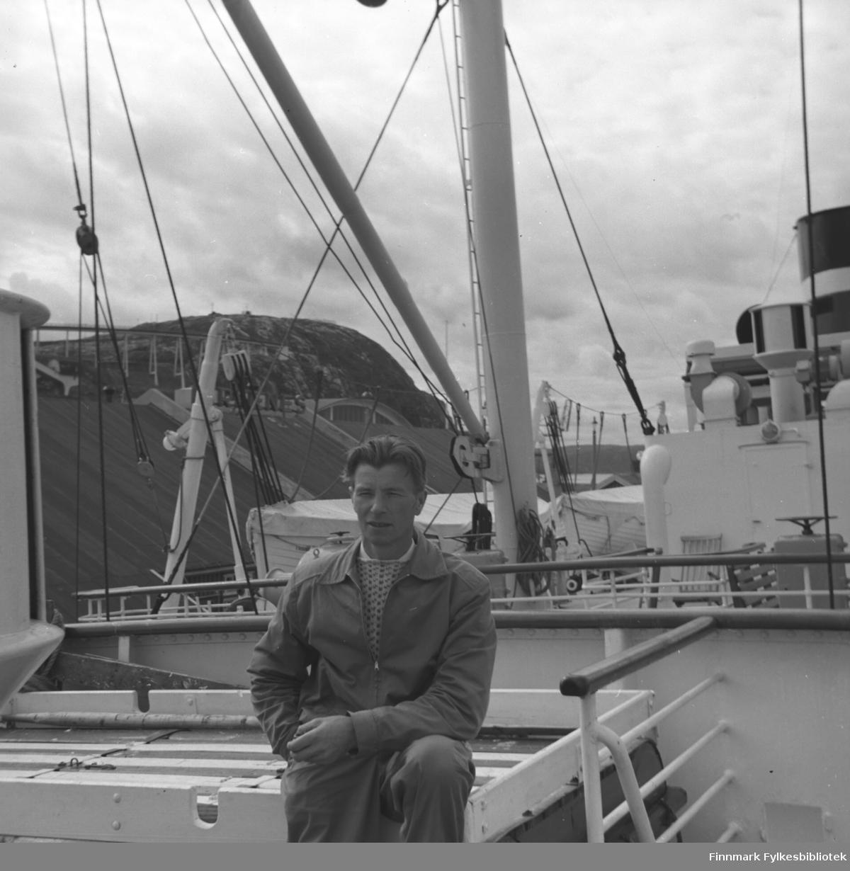 Portrett av Eino Drannem, sittende på dekket av hurtigruta Erling Jarl.