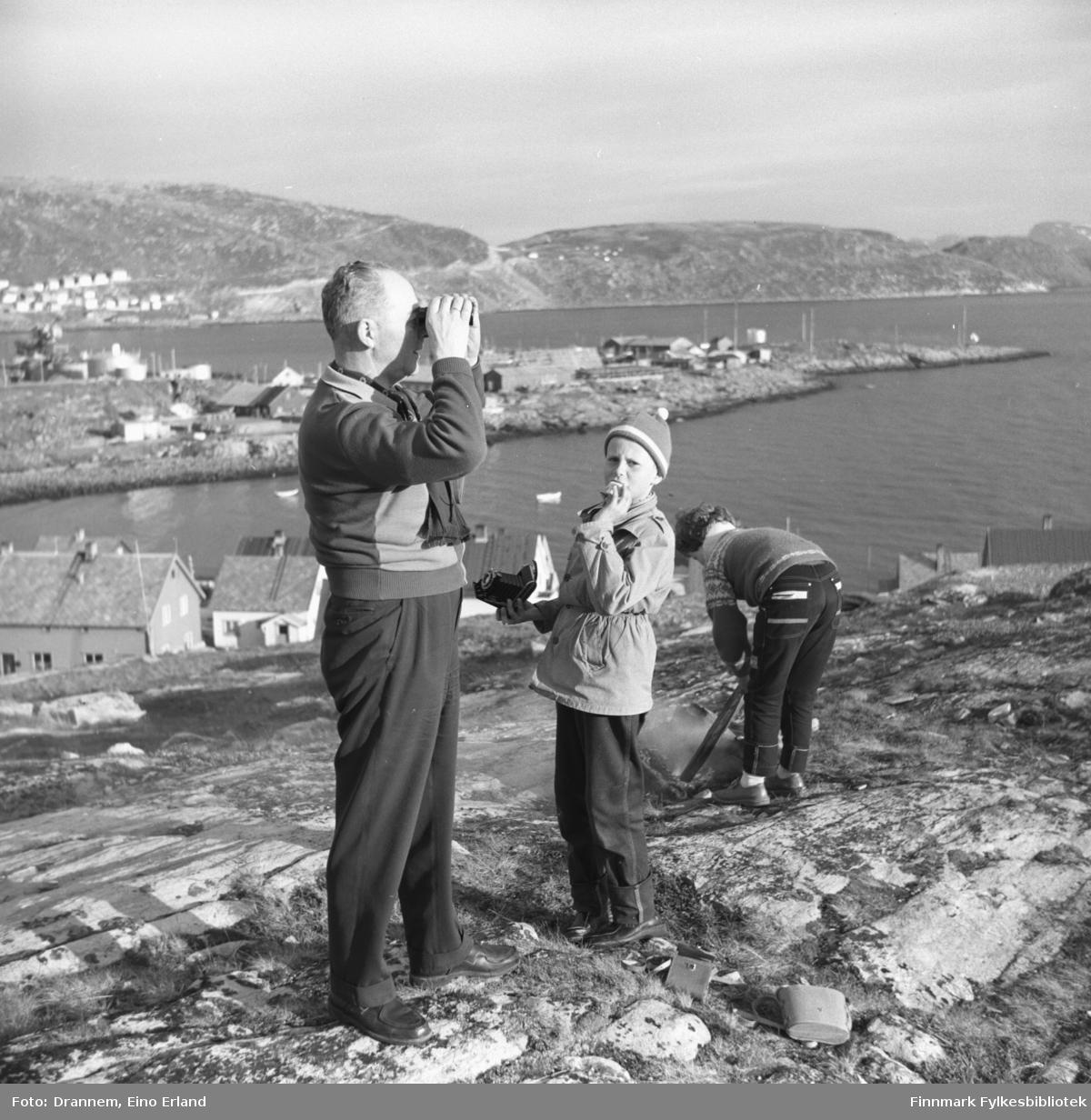 Tre personer i terrenget ovenfor Fuglenes. De er fra venstre: Olav Sørensen, Gunnar Sørensen og Turid Karikoski. Fuglenesodden stikker ut i sjøen midt på bildet.  Fotografiet kan være tatt på St Hansaften.