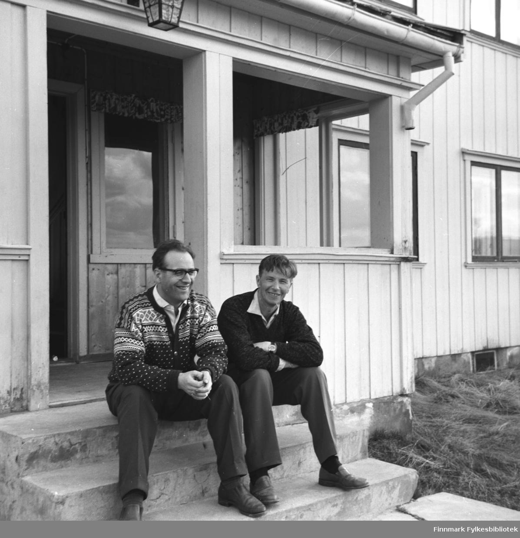 To menn sitter på trappa til en bygning i Karasjok. Mannen til venstre på bildet er ukjent og ved siden av han sitter Eino Drannem.