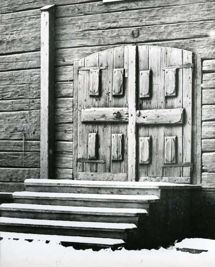 En port med pardörrar vid en byggnad i Hassela.
