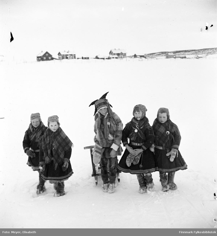 Skolebarn. Fire jenter flankerer en gutt med spark. Alle kledd i samiske kofter og gutten i samisk pesk. Fotografert av Elisabeth Meyer i Kautokeino ved påsketider 1940. I bakgrunnen Prestegården og Lensmannsgården i Kautokeino.