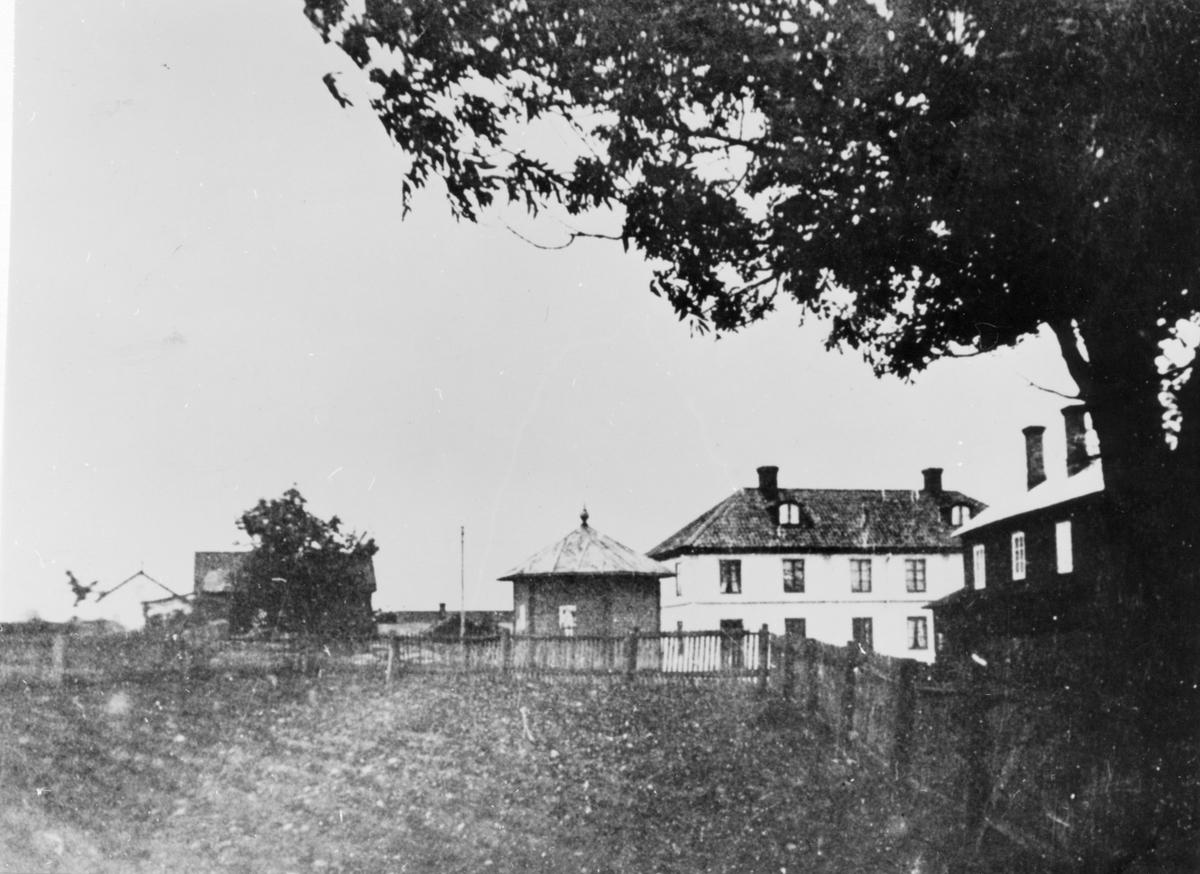 Vy från Brunn 1871. Bilden tagen från platsen där nuvarande slaktare Petterssons fastighet står. Det mångkantiga huset är spruthuset, stående mitt på torget till mitten av 1950-talet. Det ägs nu av Einar Lundbergs sterbhus. Den vita byggnaden byggdes 1850 av handlanden Hedenström som affärslokal, nu (1985) ägd av Gunder Hedblom och används som bostadshus, tidigare fanns där en läkarmottagning. Högra byggnaden är Norrgårds. Vägen till Rångsta går mellan Norrgårds och staketet. Det instängda området med potatisland är tomten där fotograf Erixons fastighet stod, nu riven med väg över tomten. Huset till vänster finns ingen uppgift om.