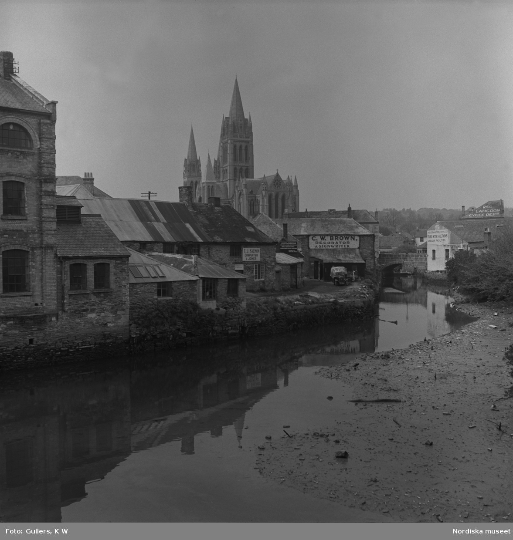 Bebyggelse nära flod i förgrunden. Stor kyrkobyggnad i bakgrunden