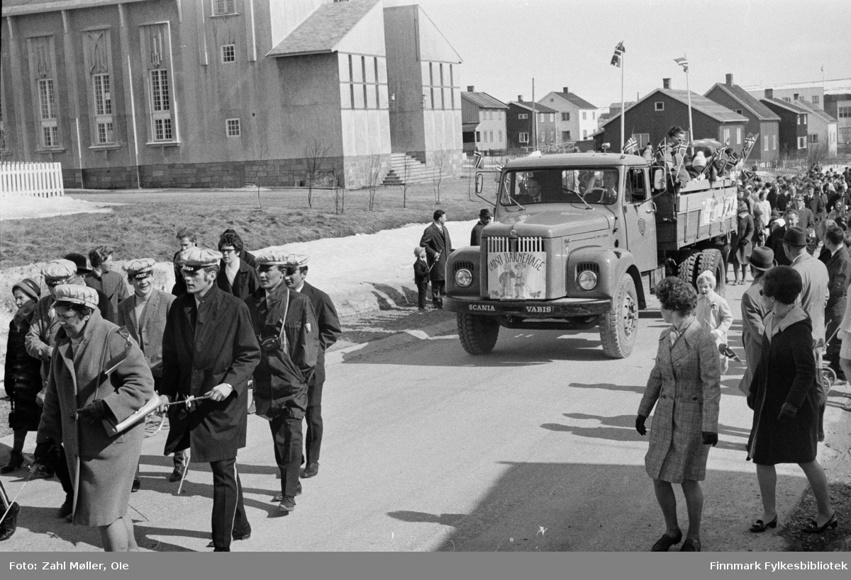 Vadsø 17.5.1969. Parade med 17.mai toget. Foran i toget sees russen, bak følger en lastebil med barnehagebarn på lasteplanet og borgertoget følger etter.  Fotoserie av Vadsø-fotografen Ole Zahl-Mölö.