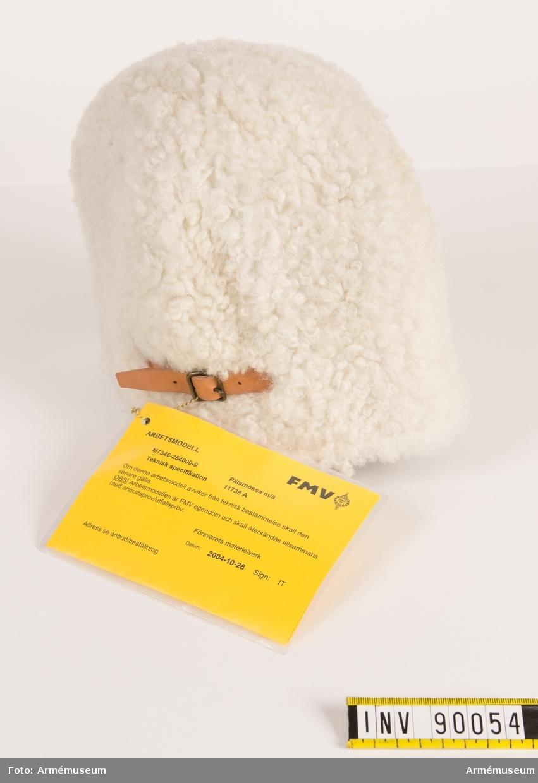 """Vit pälsmössa i äkta fårskinn. Foder i bomull/polyester. Nationalitetsmärke fram, läderrem med spänne bak.  Vidhängande modellapp med text: """"FMV. Arbetsmodell. M7346-254000-9 älsmössa m/ä. Teknisk specifikation 11738 A. Om denna arbetsmodell avviker från teknisk bestämmelse skall den senare gälla. OBS! Arbetsmodellen är FMV egendom och skall återsändas tillsammans med anbud/utfallsprov. Försvarets materielverk. Datum: 2004-10-28 Sign: IT. Adress se anbud/beställning."""