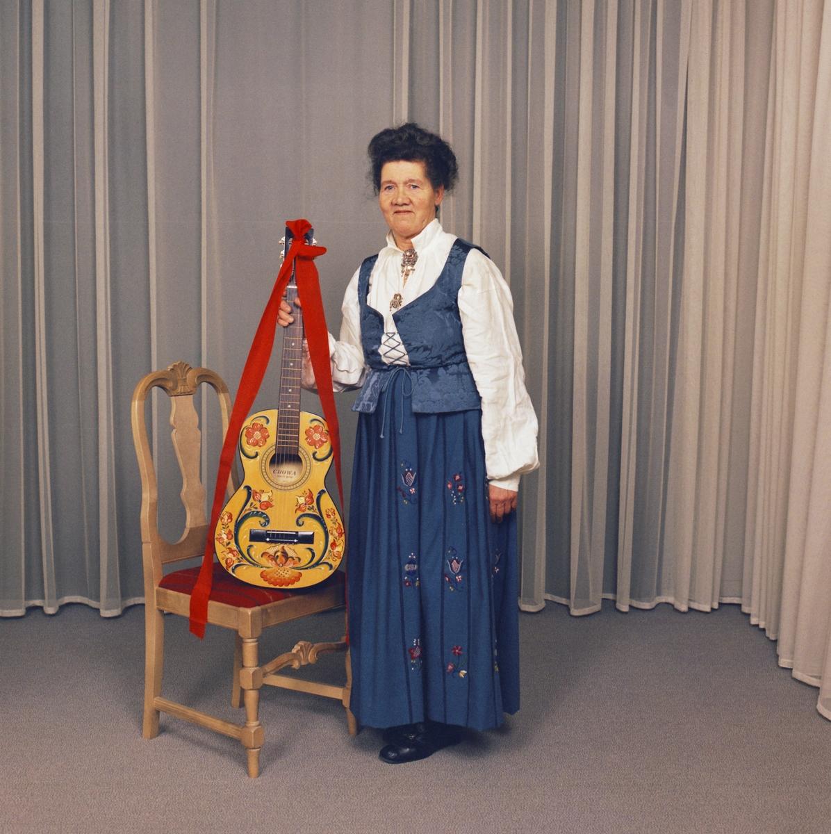 Bunadskledd kvinne med rosemaltgitar fotografert i studio på Strømmen