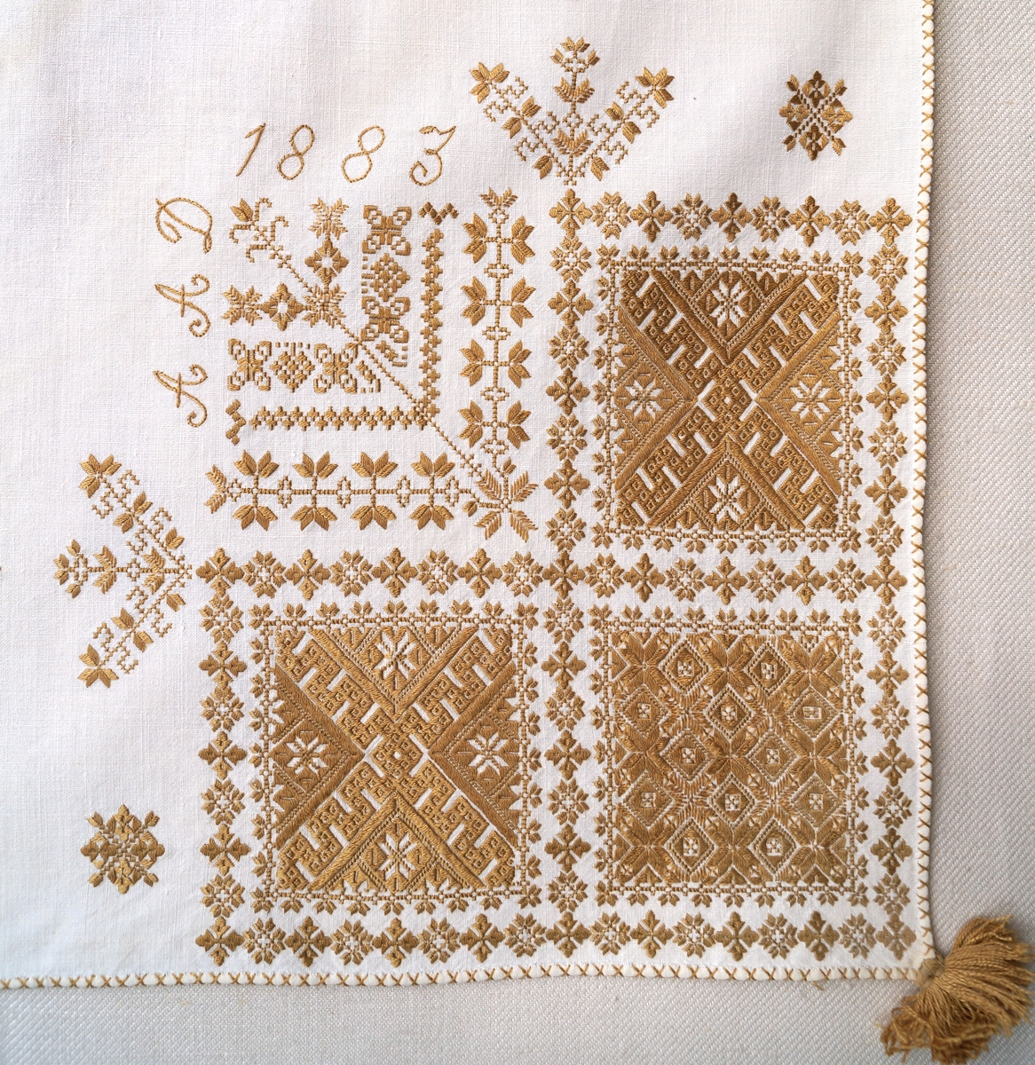 Blomsterliknande och geometriskt mönster samt märkning med årtal och initialer.  Bård mellan ryggsnibb och framsnibbar svastikliknande.  Ornament: Figurer i plattsöm