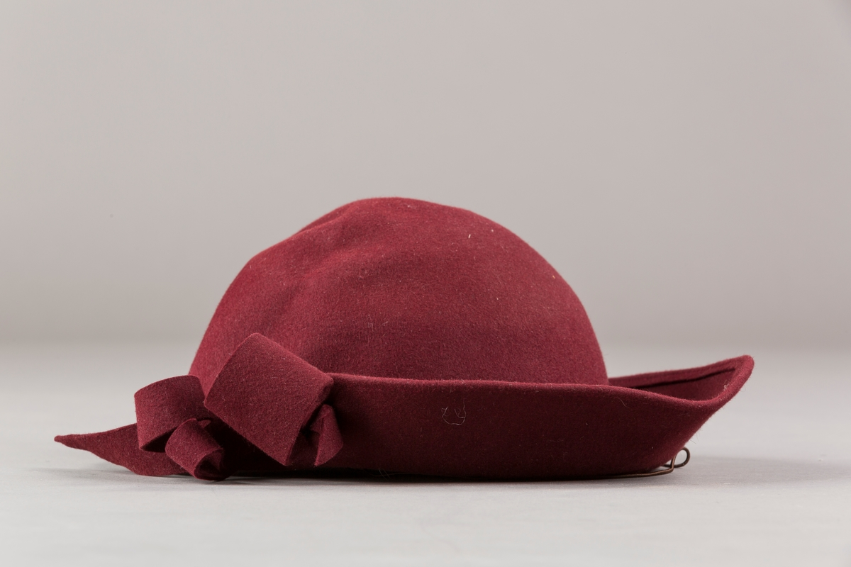 Form: Sirkelformet, avrundet  med asymetrisk brem og sløyfe. Bomullsbånd innvendig og hattestrikk