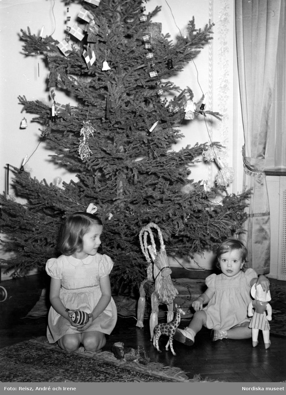 Två flickor leker med leksaker vid julgran