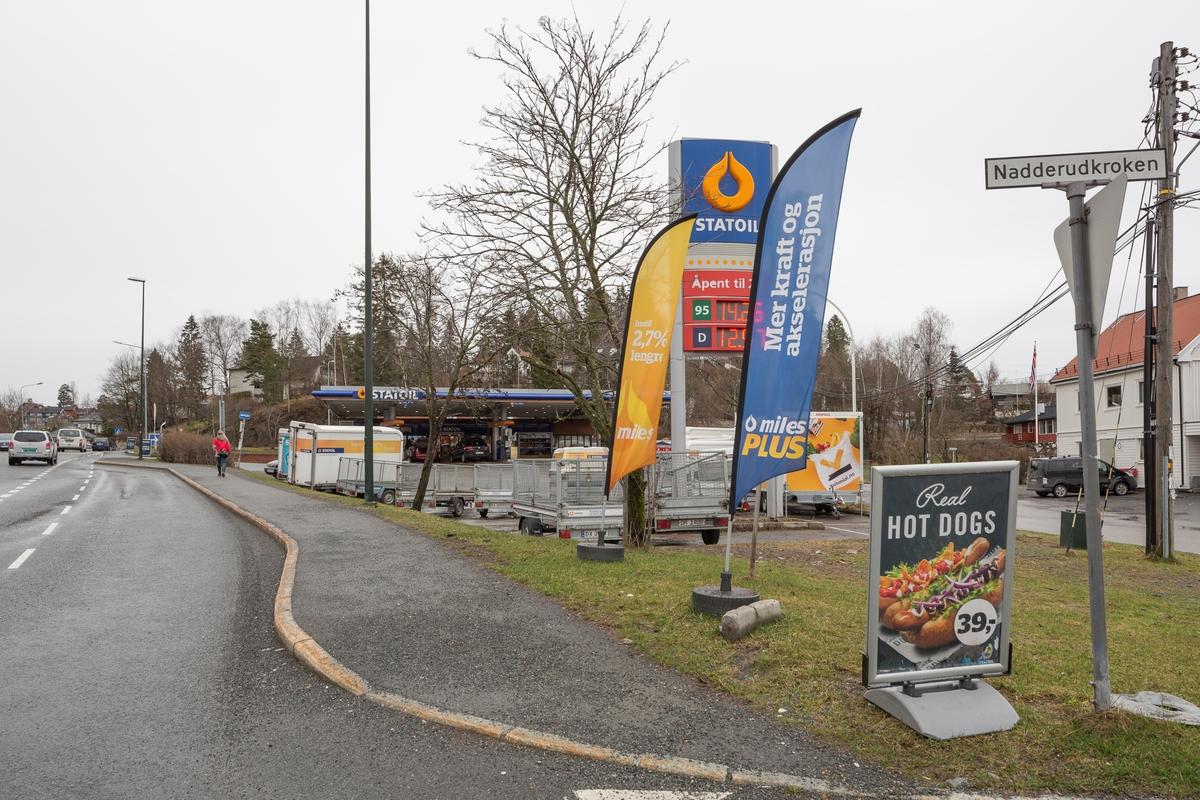 Statoil Nadderud. Veiskilt Statoil og reklamebanner. Bensinstasjon med pumpetak i bakgrunnen.