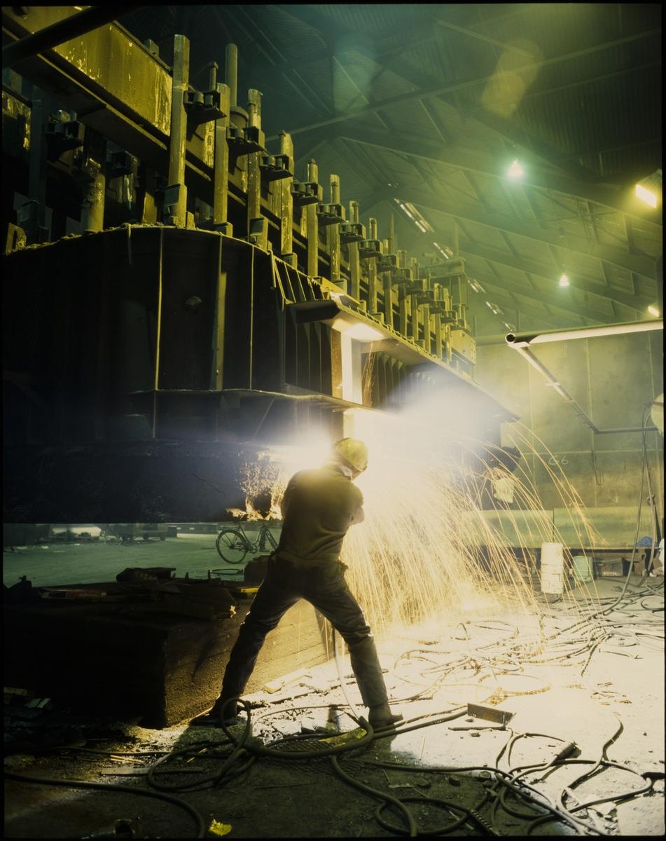 En arbeider sveiser inne på aluminiumsverket til Hydro på Karmøy.