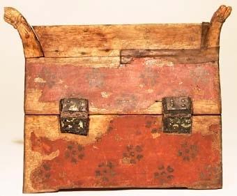 """Relikskrin av trä utformat som byggnad med sadeltak. Skrinets lock har formen av sadeltak med drakhuvudformade gavelspetsar. Mellan gavelspetsarna en list längs takåsen. I locket sitter en löst hängande bult med fjädrande hullingar. Locket fäst med gånggärn av läder och metallstycken. Framtill metallås nedfällt i träet. Låsets har formen av ett uppochnedvänt """"T"""". Skrinet har invändigt en rektangulär urholkning. Locket har en urholkning som följer takets form. Rester av fyrkantiga fötter. Röd färg med rosettliknande schablonmålning. Skrinet målat i rött med rosettliknande schablonmåleri. Rester av fyrkantiga fötter."""