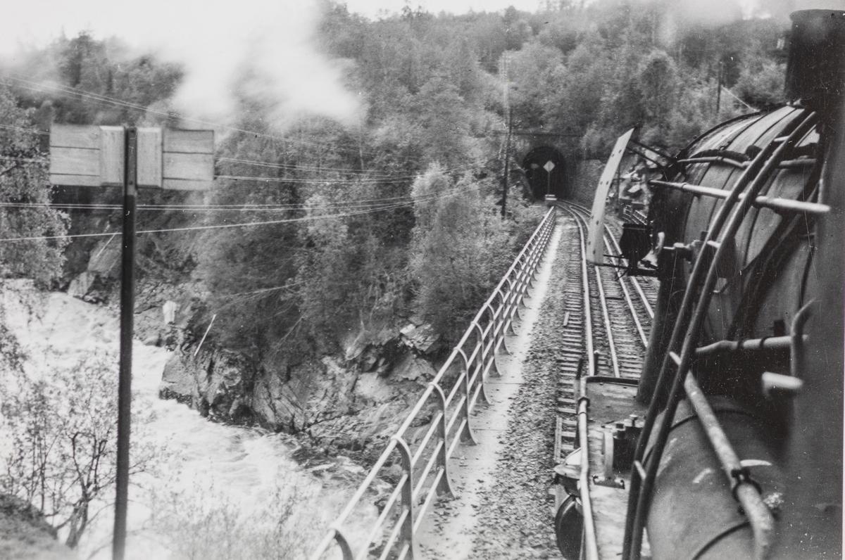 Utsikt fra fyrbøterens plass på damplokomotivet ved passering av Gulfoss bru mellom Lundamo og Hovin stasjoner på Størenbanen.
