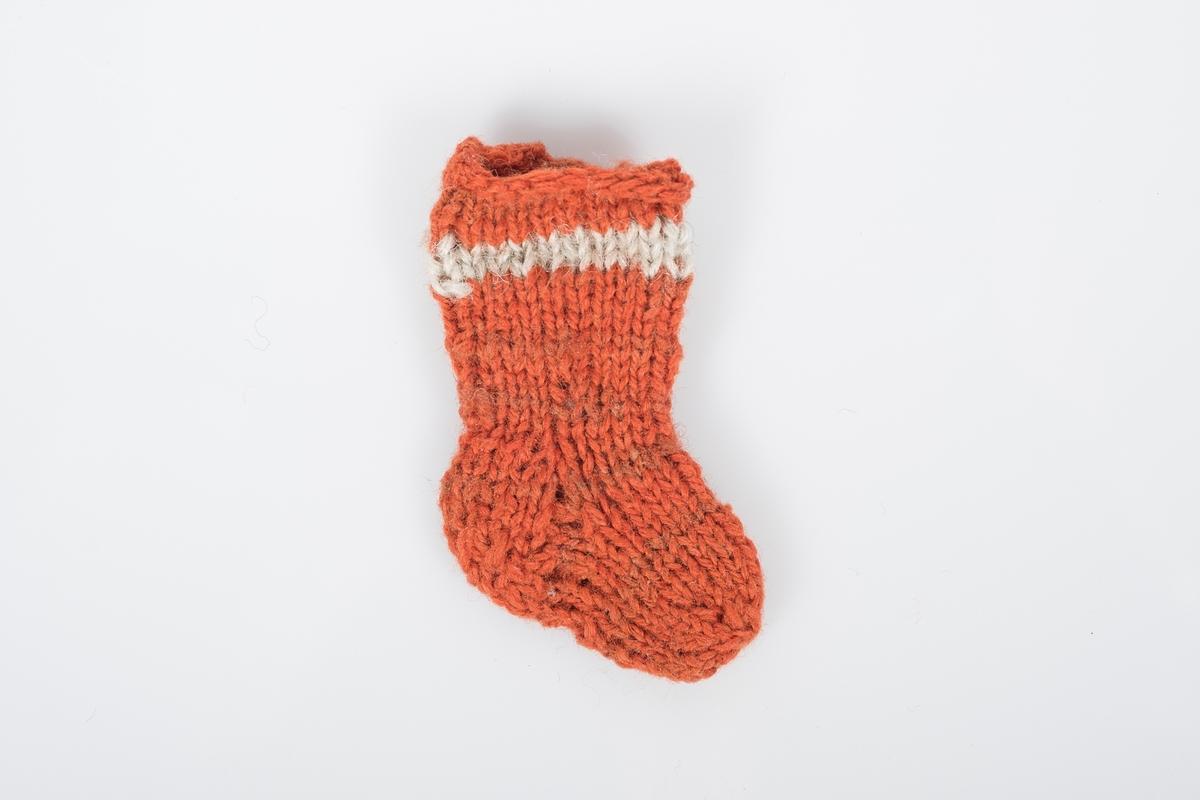 2. sokk av et par bittesmå strikkede ullsokker. Sokkene er oransjerøde med en lys stripe øverst og nøen brunrøde striper lenger ned.