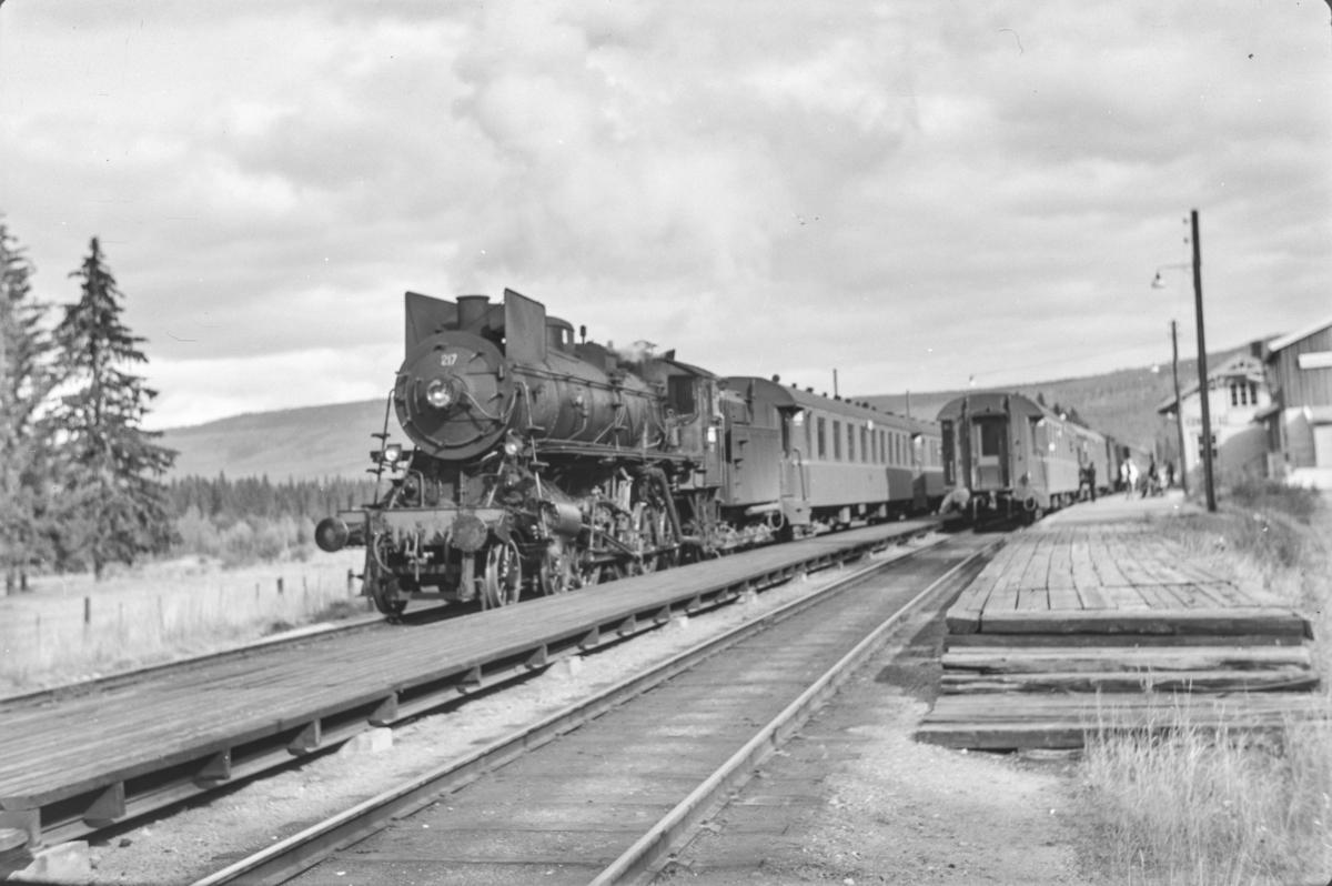 Kryssing mellom Rørosbanens dagtog på Hanestad stasjon. Til venstre dagtoget fra Trondheim til Oslo Ø, Pt. 302. Toget trekkes av damplokomotiv type 26a nr. 217.