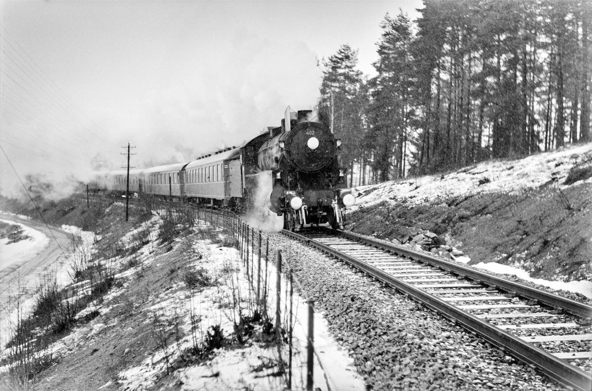 Tog 308 fra Otta ved Furuberget mellom Jessnes og Hamar. Toget trekkes av damplokomotiv type 1b nr. 402.